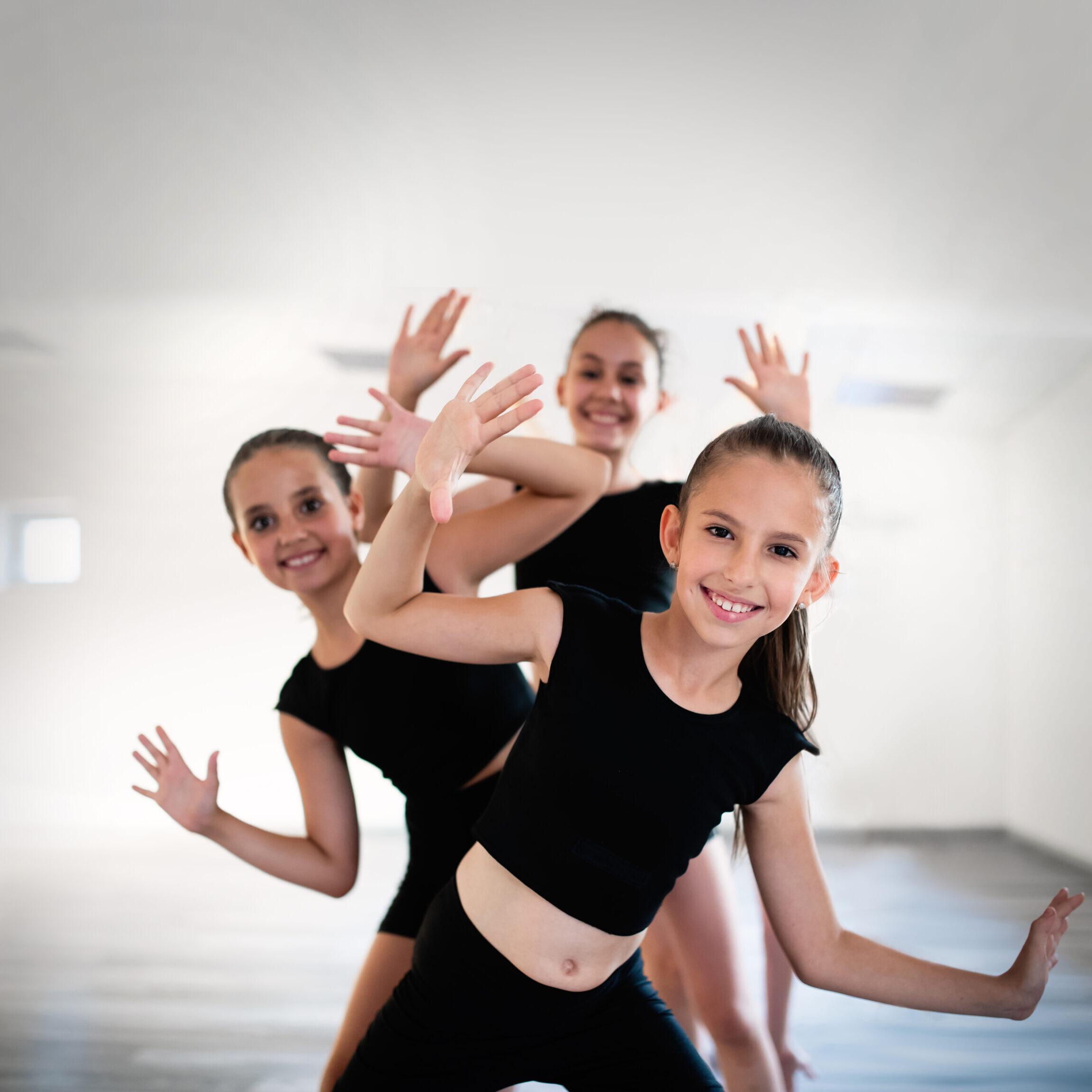 Group of fit children exercising ballet in studio together