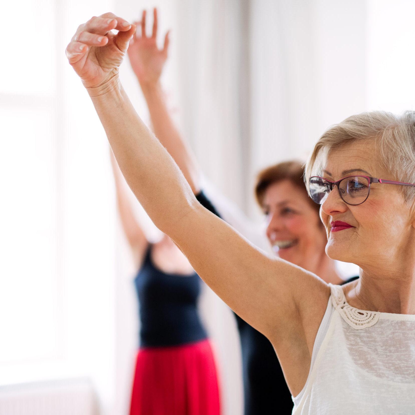 A group of female seniors attending dancing class with dance teacher.